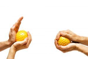 Symbolbild neurologische Ergotherapie: Zwei Hände kneten gelbe Noppenbälle