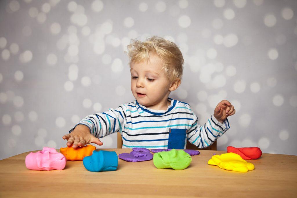 Ergotherapie Vaihingen: Pädiatrie. Kleinkind spielt mit Knete in verschiedenen