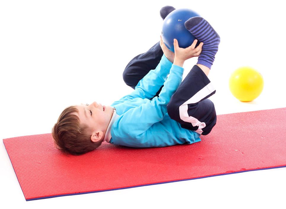 Ergotherapie Vaihingen: Pädiatrie. Kind auf Gymnastikmatte bei Übung mit Gymnastikball