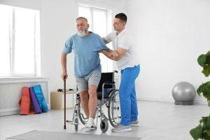 Ergotherapie Vaihingen: Intensivtraining Physiotherapeut hilft älterem Mann aus dem Rollstuhl für Gehtraining