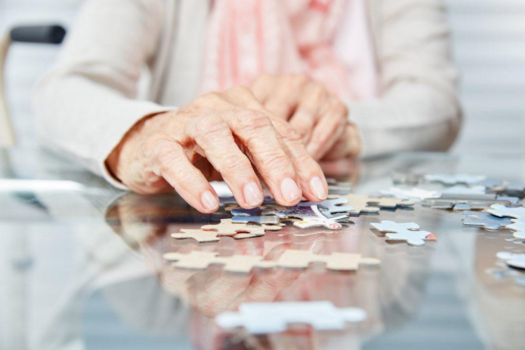 Ergotherapie Vaihingen: Geriatrie / Hände von Senioren beim Puzzle spielen