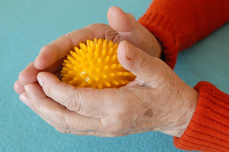 Ergotherapie Vaihingen: Geriatrie / Alte Hände halten einen gelben Massageball